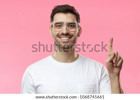 Attractive young man wearing transparent eyeglasses and white t-shirt pointing up with his finger isolated on pink background