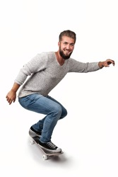 Attractive young man with a beard has fun on a skate board