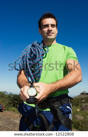 Attractive, young man with a climbing rope and compass on a camping trip