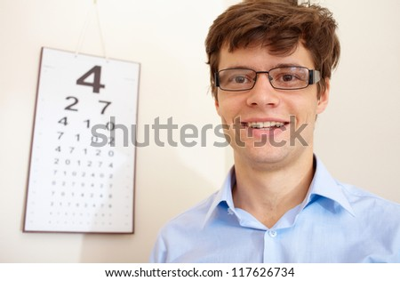 Attractive young man with an eye chart behind