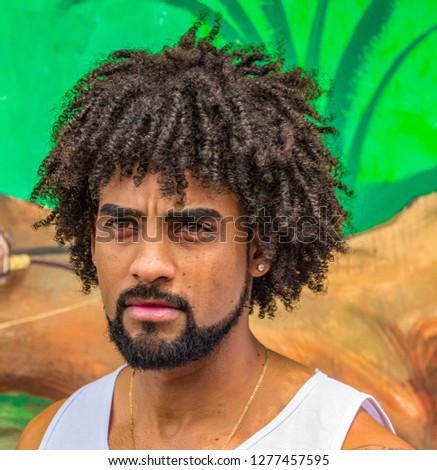 Attractive young man with curly afro hair, beard, earings and expressive eyes in thoughtful mood
