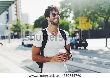 Attractive young man with dark curly hair wearing sunglasses is walking the street with a cup of coffee on a sunny day. Bearded hipster guy wearing casual clothes enjoys relaxing on a summer weekend.