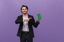 Attractive young man with dark hair, modern black suit and white shirt looking into camera, smiling and pointing on mobile phone in hand. Brunette posing isolated over violet background