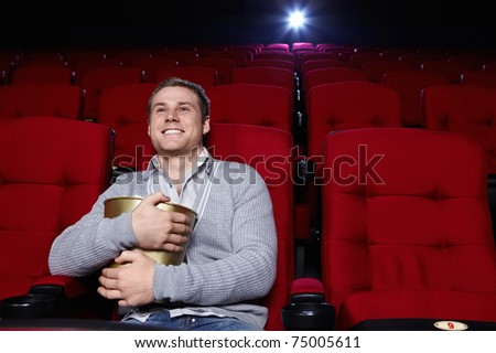 Attractive young man with popcorn watching a movie at the cinema