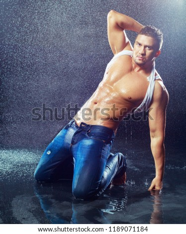 attractive young man with wet clothes under the rain  , studio photoshoot