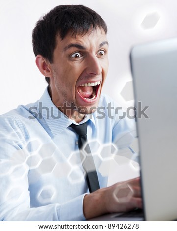 Attractive young man working with a laptop at his office. He is screaming and very expressive