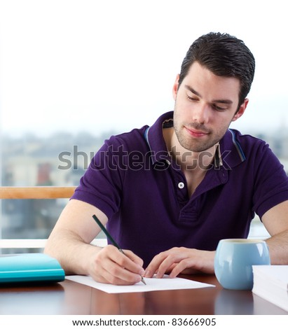 Attractive young man writes a letter by hand