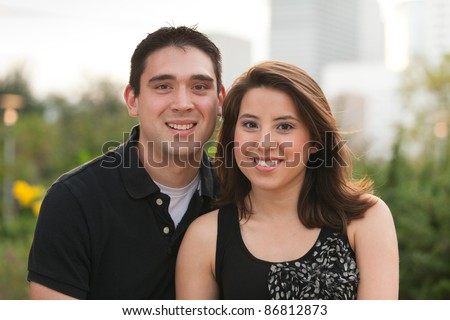 Attractive young married couple outdoors in a park setting.