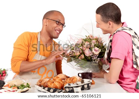Attractive young mixed ethnicity gay, homosexual couple, Caucasian and African American in kitchen, celebrating Valentine at the breakfast table.  Studio, white background.