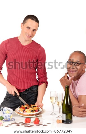 Attractive young mixed ethnicity gay, homosexual couple, Caucasian and African American in kitchen, enjoying a fruit pie and  champagne.  Studio, white background.