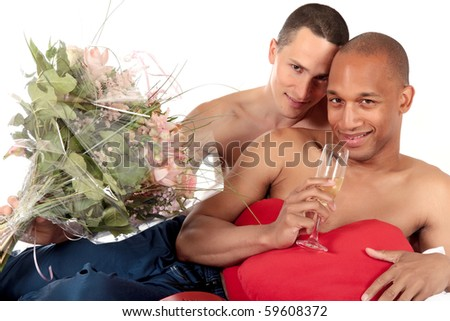 Attractive young mixed ethnicity gay, homosexual couple, Caucasian and African American men in the bedroom, celebrating valentines day with champagne and bouquet of flowers.