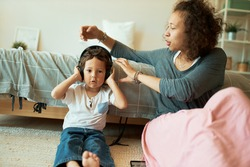Attractive young mixed race mother babysitting her toddler son who is sitting on floor in wireless headphones, listening to children songs online via mp3 player. Fun, entertainment and technology