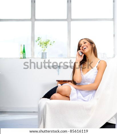 Attractive young mixed race woman relaxes at home, chatting on the phone with her friend