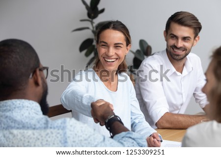 Attractive young mixed race woman shaking hands with black partner starting negotiations sitting together in office boardroom with colleagues company members millennial staff feels good and satisfied