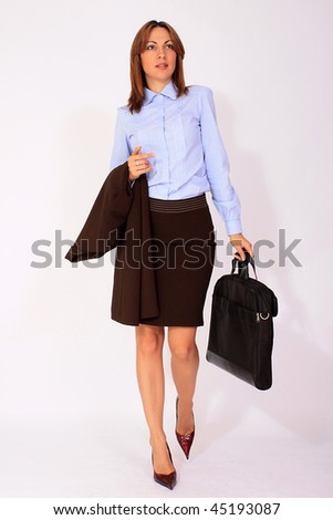 Attractive young modern businesswoman walking with briefcase in her hand