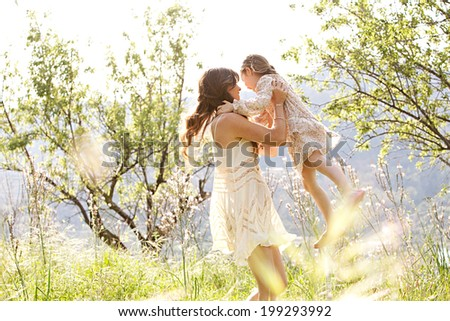 Attractive young mother and her beautiful daughter playing together in a spring garden with flowers and sunshine, carrying the child in her arms and joyfully turning around, smiling. Family lifestyle.
