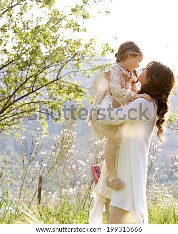 Attractive young mother and her beautiful daughter playing together in a spring garden with flowers and sunshine, carrying the child in her arms and joyfully smiling. Family outdoors lifestyle.