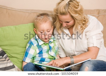 Attractive young mother reading a book with her son.