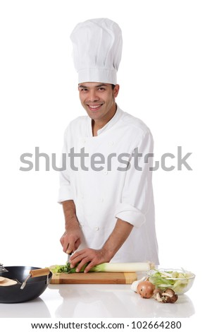 Attractive young nepalese chef male with uniform and hat, cutting a leek. Utensils and ingredients on table. Studio shot. White background.