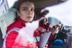 attractive young paramedic sitting in ambulance and looking away