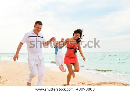 Attractive young parents playing with their little son - stock photo