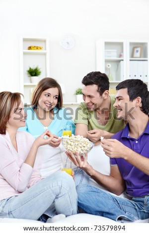 Attractive young people eating popcorn