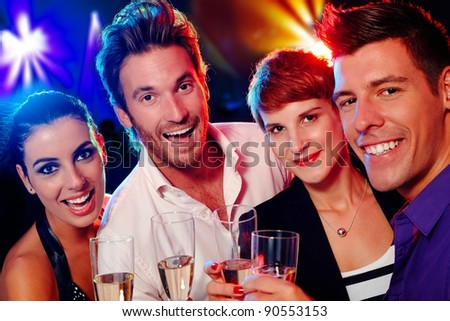 Attractive young people smiling happily in nightclub
