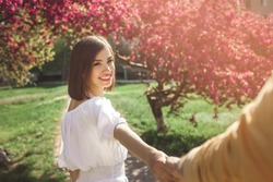 Attractive young people walking in park. Pretty couple together. Woman and man inlove. Girl taking her boyfriend by the hand outdoor