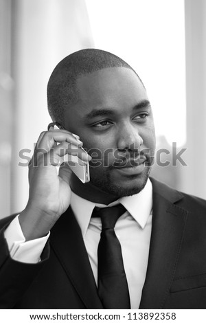 Attractive, Young Professional African American Businessman Holding Phone and Talking