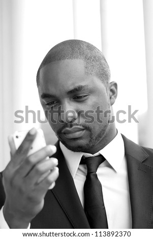 Attractive, Young Professional African American Businessman Holding Phone and Texting