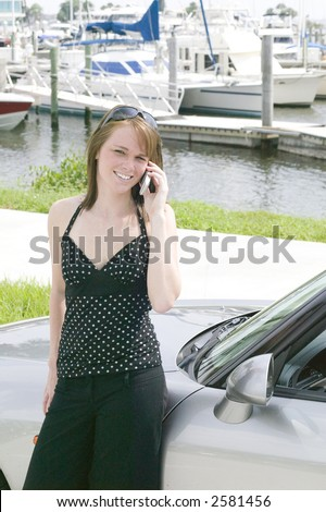 Attractive young red head business woman stays in touch on the go with the latest technology in cell phones and laptops