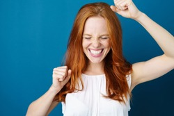 Attractive young redhead woman celebrating a victory punching the air with her fists and a beaming toothy smile over a blue studio background with copy space