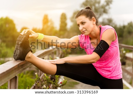 Attractive young runner woman doing stretching exercises.