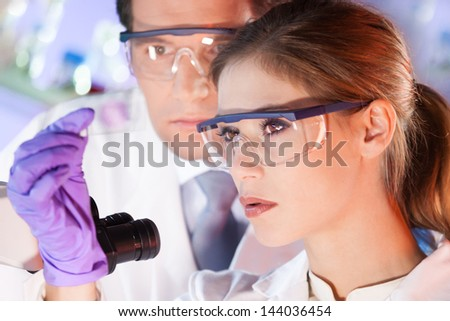 Attractive young scientist and her post doctoral supervisor looking at the microscope slide in the forensic laboratory.