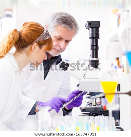 Attractive young scientist and senior male supervisor checking experiment protocol at tablet laptop computer in life science research laboratory (biochemistry, genetics, forensics, microbiology)