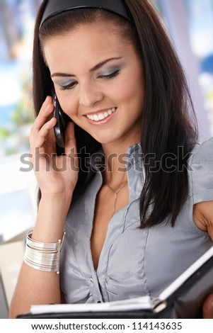 Attractive young secretary talking on mobile, looking at organizer, smiling.