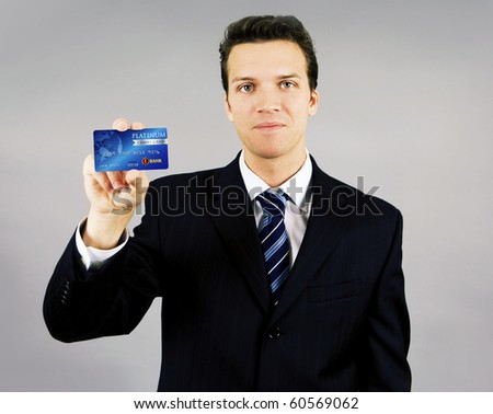 Attractive young smiling business man holding a credit card