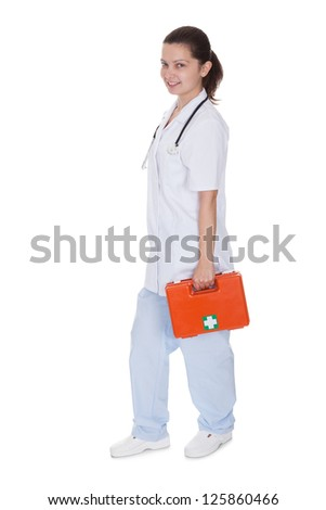 Attractive young smiling female nurse or doctor carrying a portable first aid kit isolated on white
