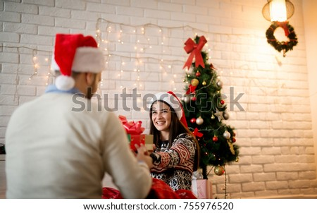 Attractive young smiling girl with Santa hat receiving Christmas gift from boyfriend.