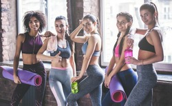 Attractive young sport girls are having rest after doing yoga together. Group training. Healthy lifestyle concept.