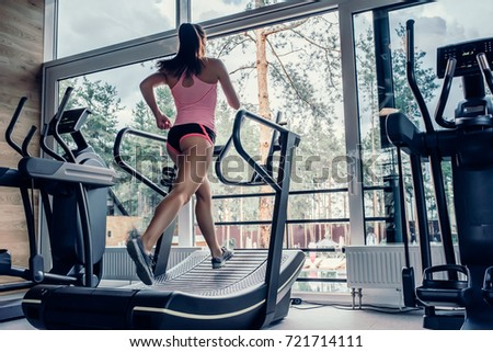 Attractive young sports woman is working out in gym. Doing cardio training on curve treadmill. Running on non-motorized treadmill.