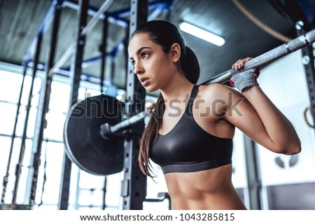 Attractive young sporty woman is working out in gym. Cross fit training. Muscular woman is squatting with barbell
