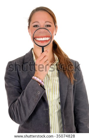 Attractive young successful female businesswoman with magnifying glass in front of mouth.  studio shot.