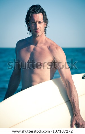 Attractive young surf man portrait at the beach with a surfboard.