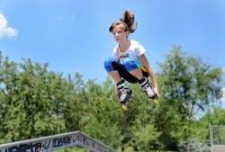 Attractive young teenage girl jumping in the air on rollerblades as she jumps off a ramp at a skate park
