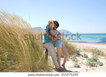 Attractive young tourist couple enjoying a summer holiday together on beach with blue waters and grass sand dunes, hugging and kissing in romantic summer honeymoon, outdoors nature. Travel lifestyle.