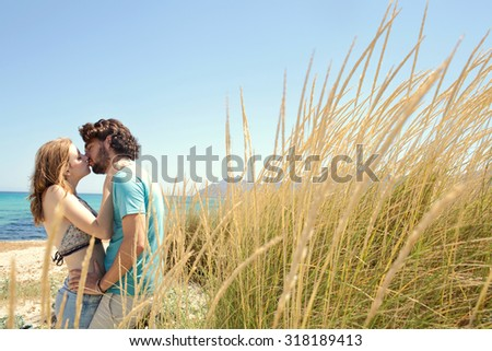 Attractive young tourist couple hugging and kissing on the lips standing on a beach with blue sky and long grass dunes on a summer holiday outdoors. Travel and honeymoon lifestyle, nature exterior.