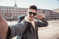 Attractive young tourist student man with backpack having fun happy and excited taking funny face selfie with smart phone in Plaza Mayor, Madrid, Spain. Vacation, and travel around the world concept.