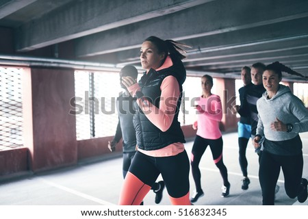 Attractive young urban runner pacing her team mates as she sprints through an undercover car park in a health and fitness concept
