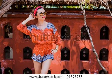 Attractive young woman among the Asian wall. Vacation. Tropics. Fashion shot.